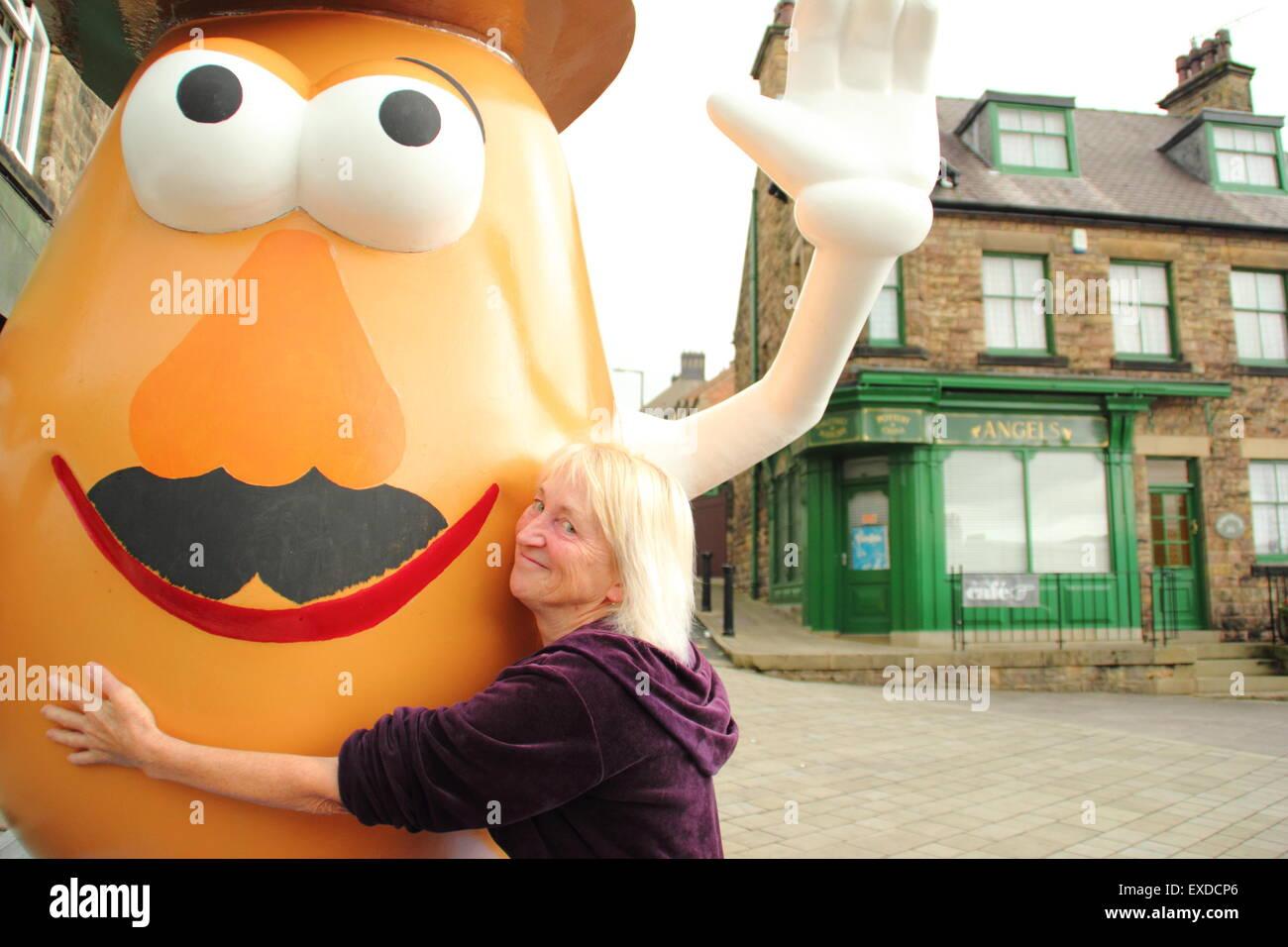 Belper, Derbyshire, UK. 12th July, 2015. Spud fan, Freda Raphael hugs a giant Mr Potato Head that has re-appeared - Stock Image