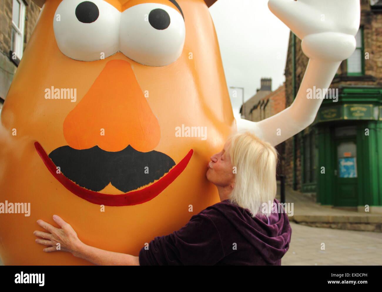Belper, Derbyshire, UK. 12th July, 2015. Spud fan, Freda Raphael plants a kiss on a giant Mr Potato Head that has - Stock Image