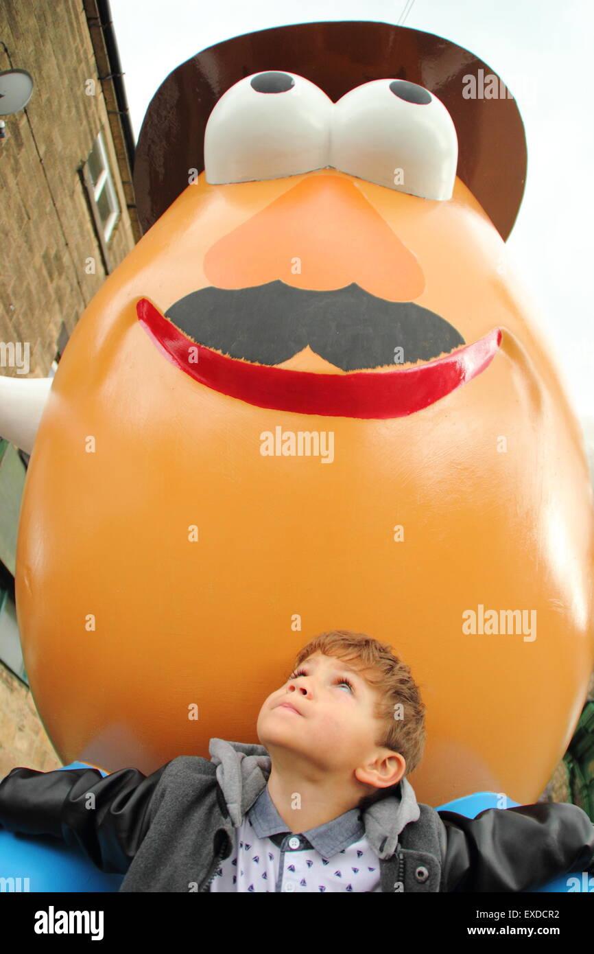 Belper, Derbyshire, UK. 12th July, 2015. Three-year-old Darwyn Reed from Belper gazes up at a giant Mr Potato Head - Stock Image