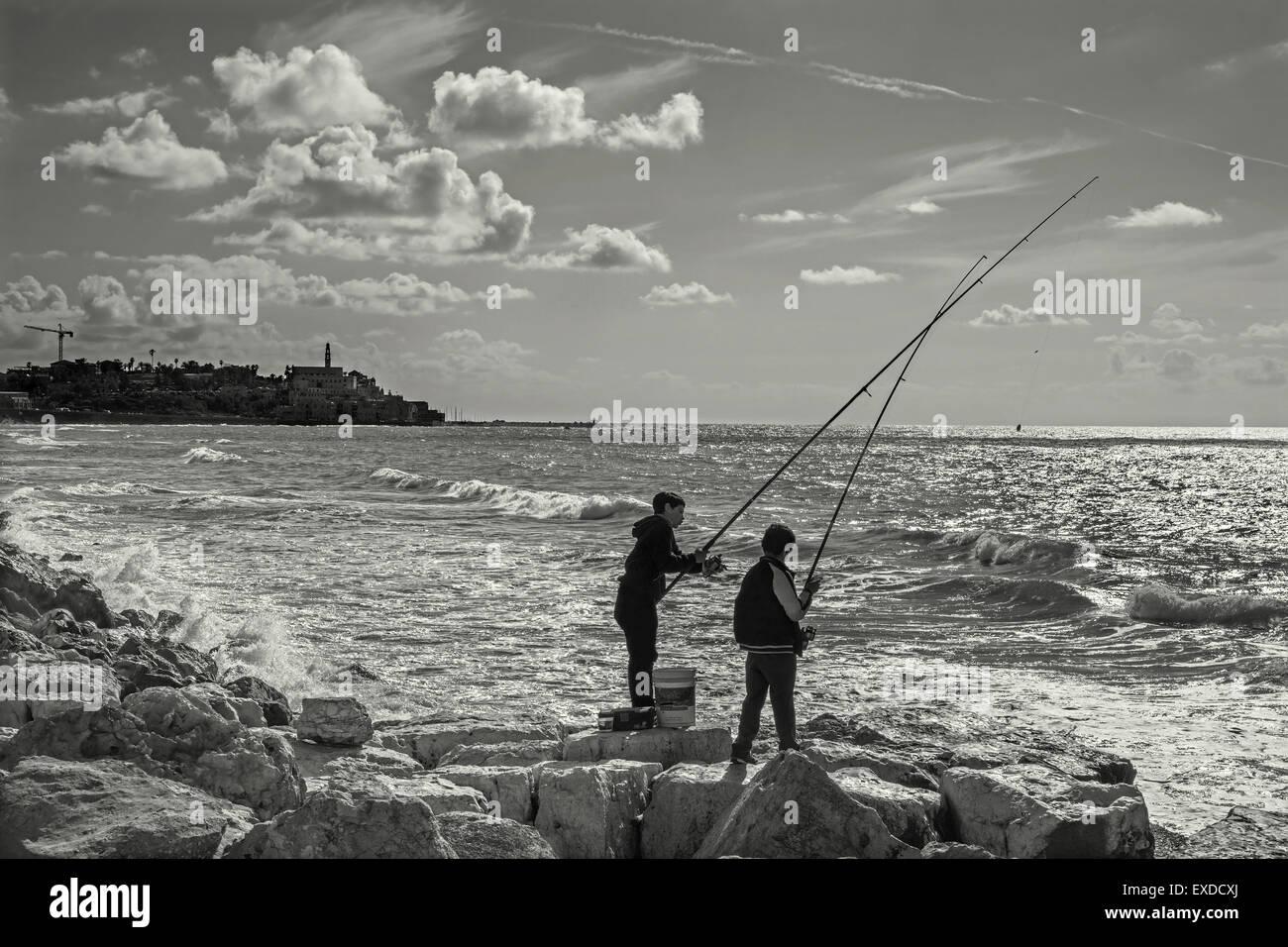 TEL AVIV, ISRAEL - MARCH 2, 2015: The fishing of boys on the seaside in Tel Aviv - Stock Image