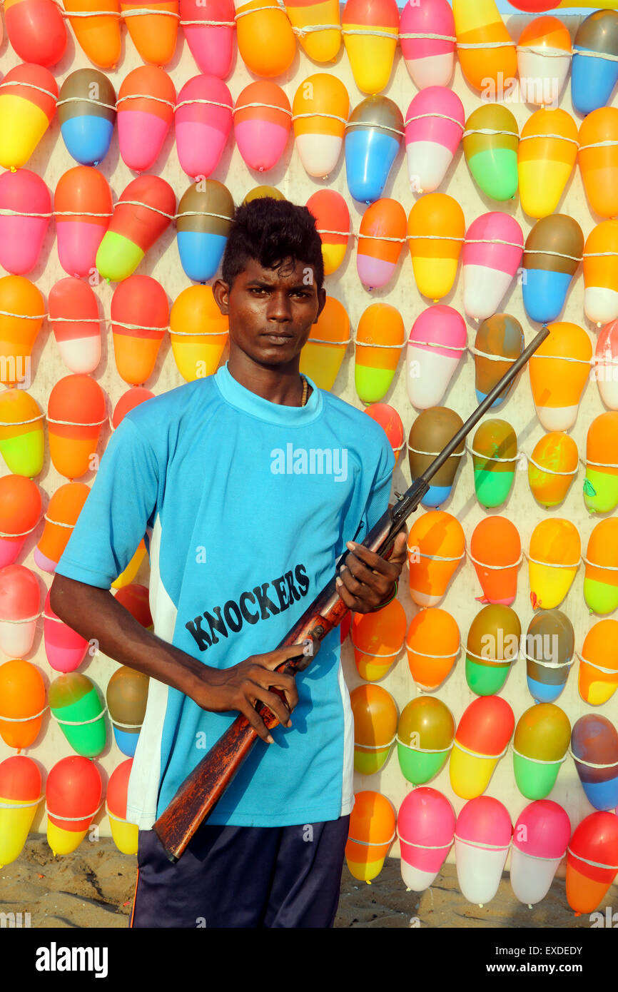 Young Indian man holds air rifle at beach fun stall with balloon targets - Stock Image