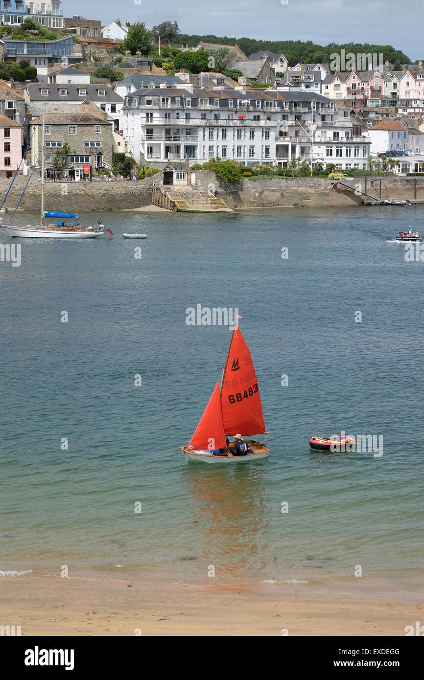 Salcombe, Devon, UK. Small Yacht with red sail on the river at Salcombe. Stock Photo