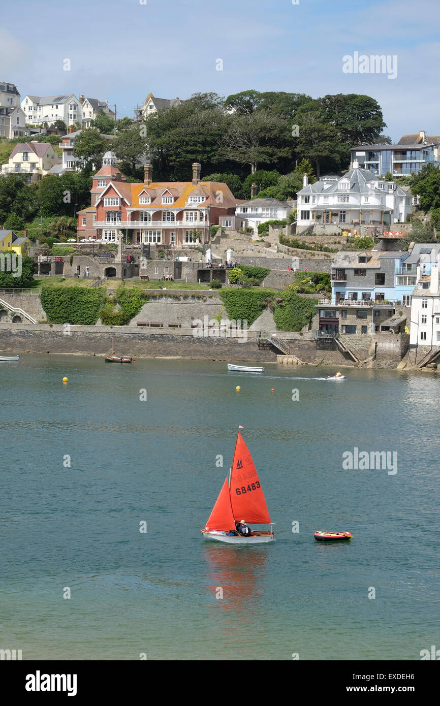Salcombe, Devon, UK. Small yacht with red sail sailing on the river at Salcombe. - Stock Image