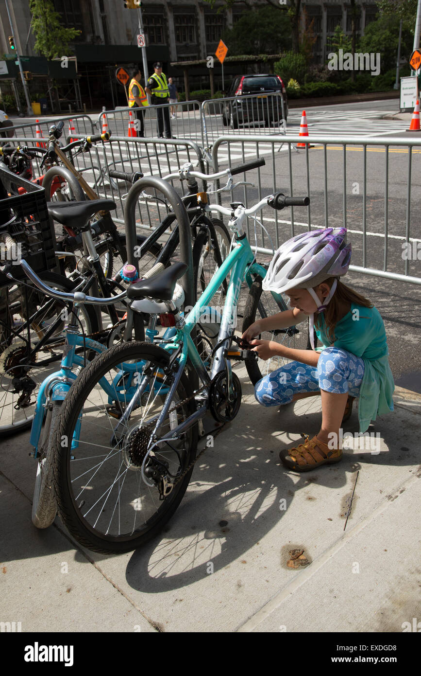 Young cyclist locking her bicycle on the roadside Upper West Side New York USA - Stock Image