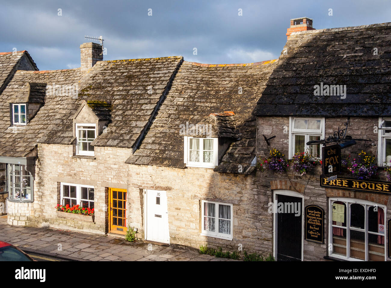 Typical old world English village scene, row of cottages with uneven roofs, Corfe, Dorset, dark skies, view along - Stock Image