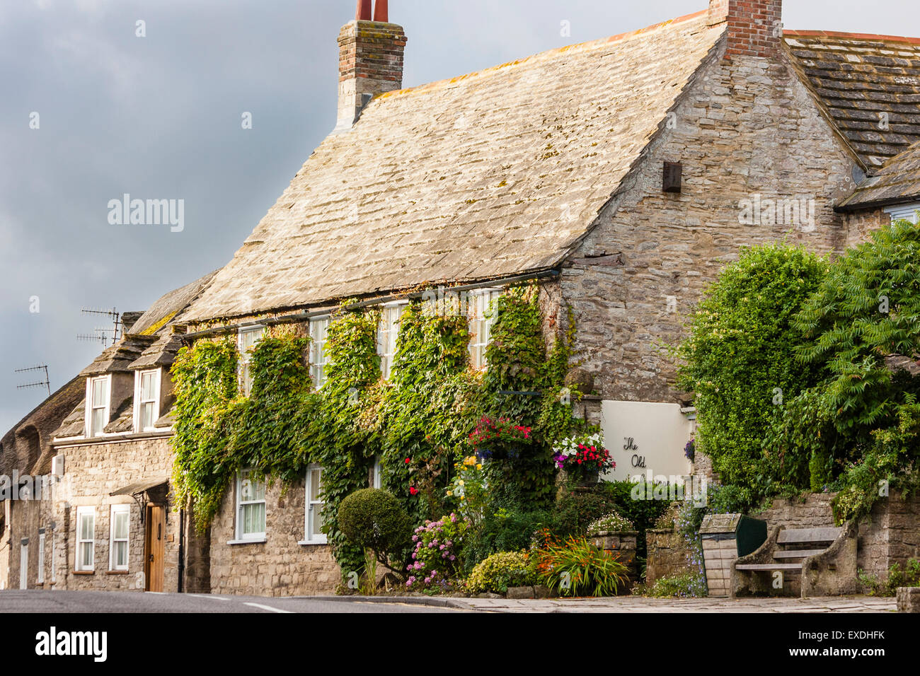 Typical old world English village, large stone house covered in ivy, Corfe, Dorset, dark skies, view along - Stock Image