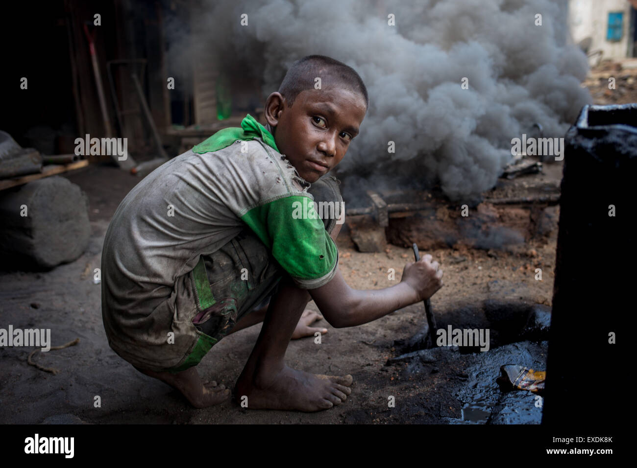Dhaka, Bangladesh. 12th July, 2015. A child works in a hazardous working condition in a Shipyard. Credit:  Mohammad - Stock Image