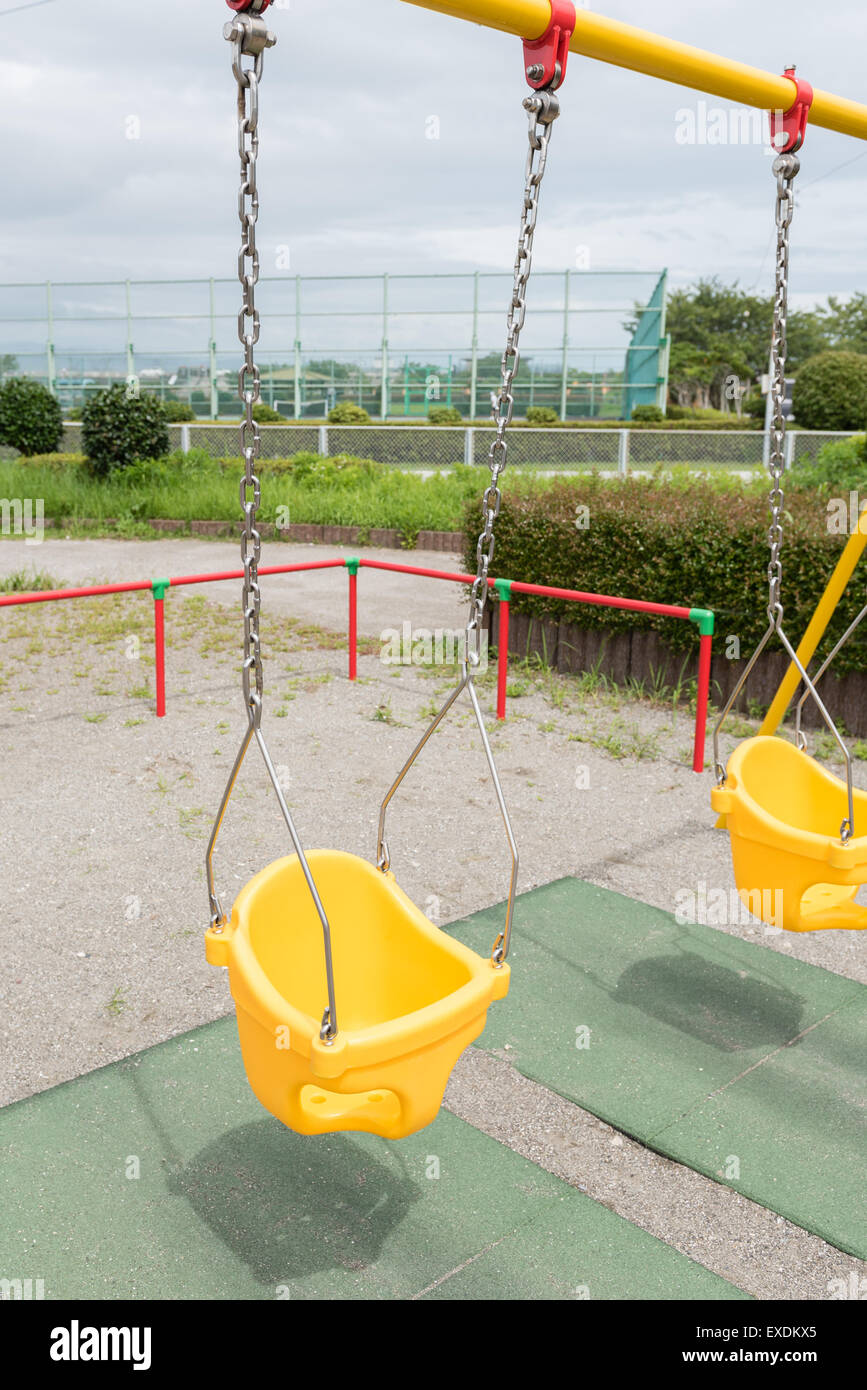 Colorful swings at a childrens park on a dark cloudy day. - Stock Image