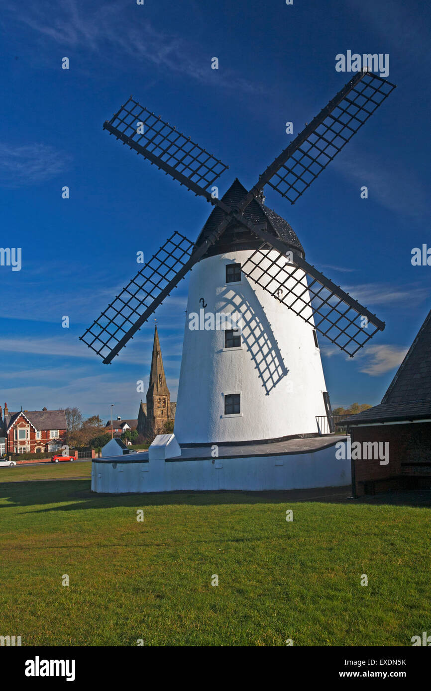 Vertical image of Windmill with church in background on Lytham green, Lancs - Stock Image