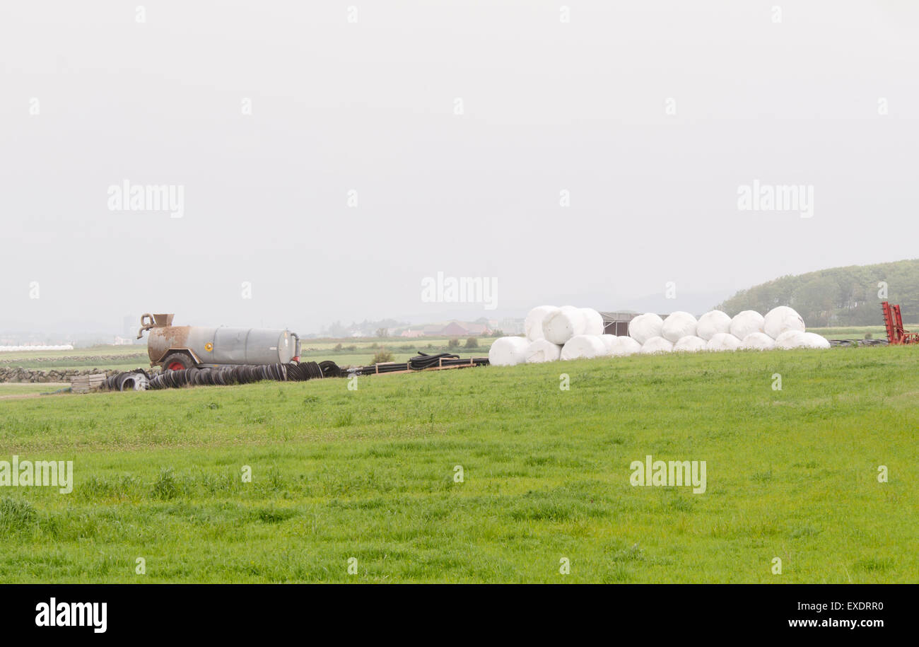 Typical flat agricultural landscape in Jaeren Norway fields, stonewalls  a manure spreader and silage bales - Stock Image