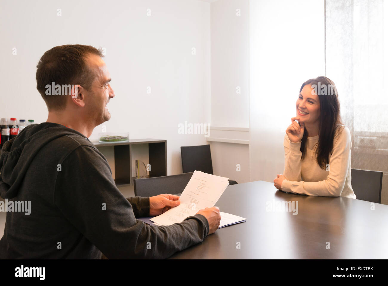 Young female candidate smiling very relaxed during job interview - Stock Image