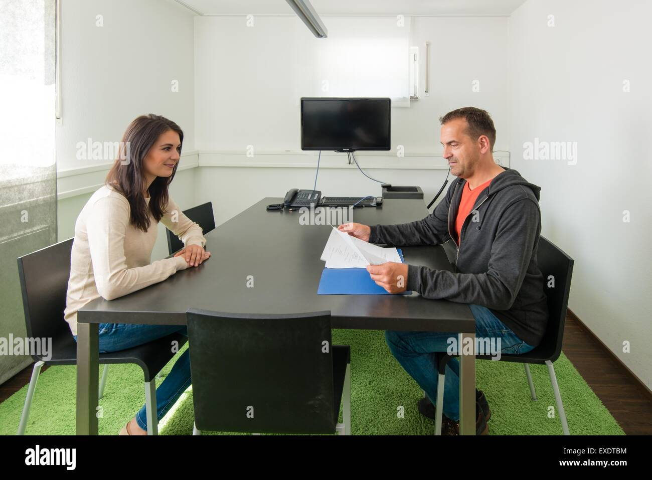 Smiling young female candidate during job interview - Stock Image