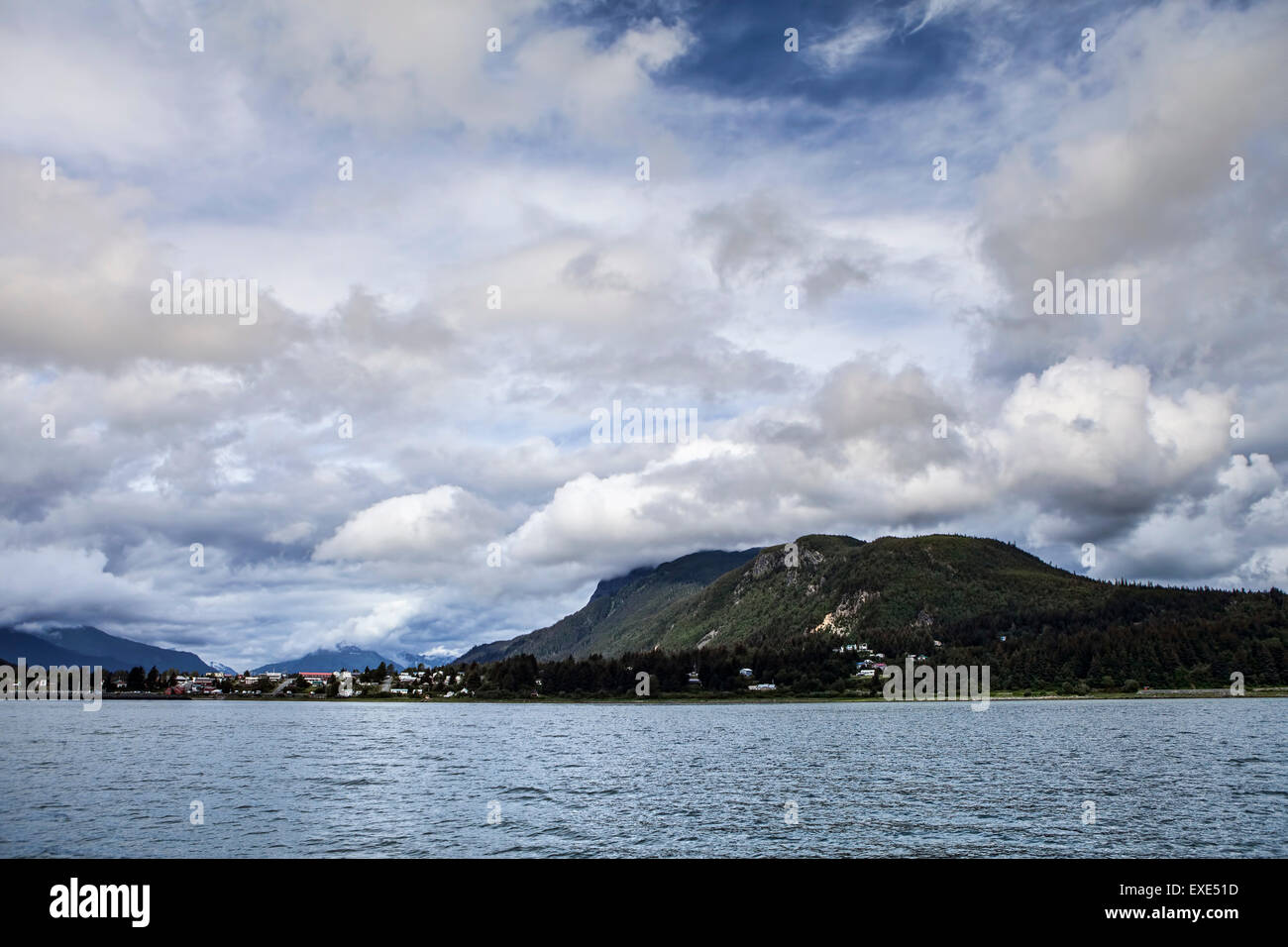 Skagway with summer clouds as seen from a boat - Stock Image