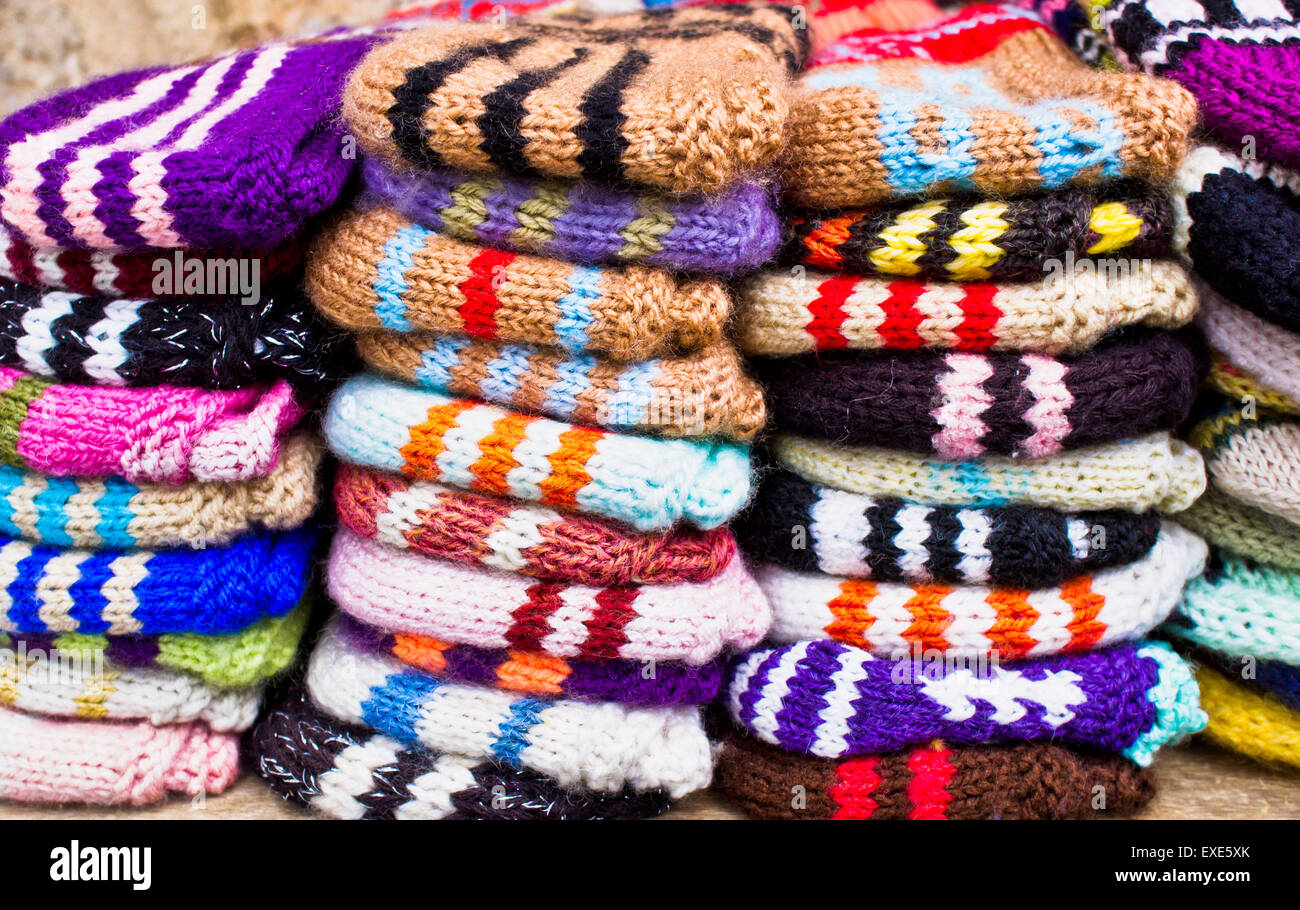 Stacks of colorful wool socks at a market - Stock Image