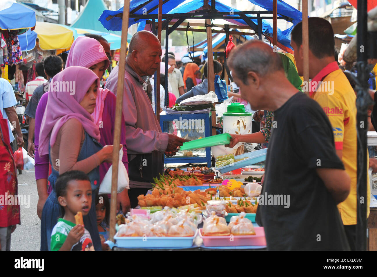 Lhokseumawe, Indonesia. 12th July, 2015. Some shoppers thronged the markets of Ramadan in the village rivet Along - Stock Image
