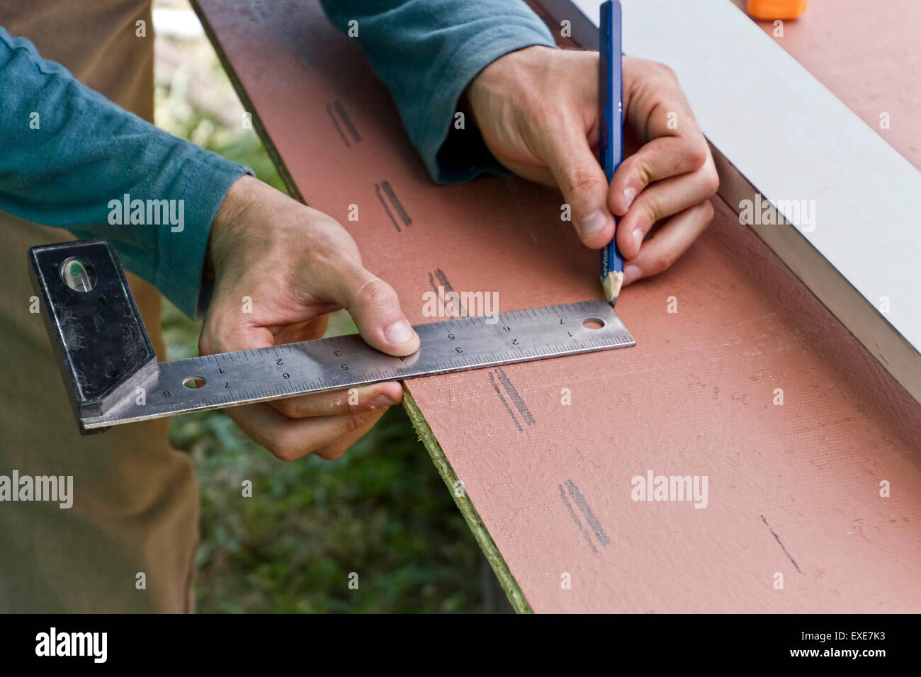 Close up of a young man's hands using a metal ruler with level to mark construction measurements on a piece - Stock Image