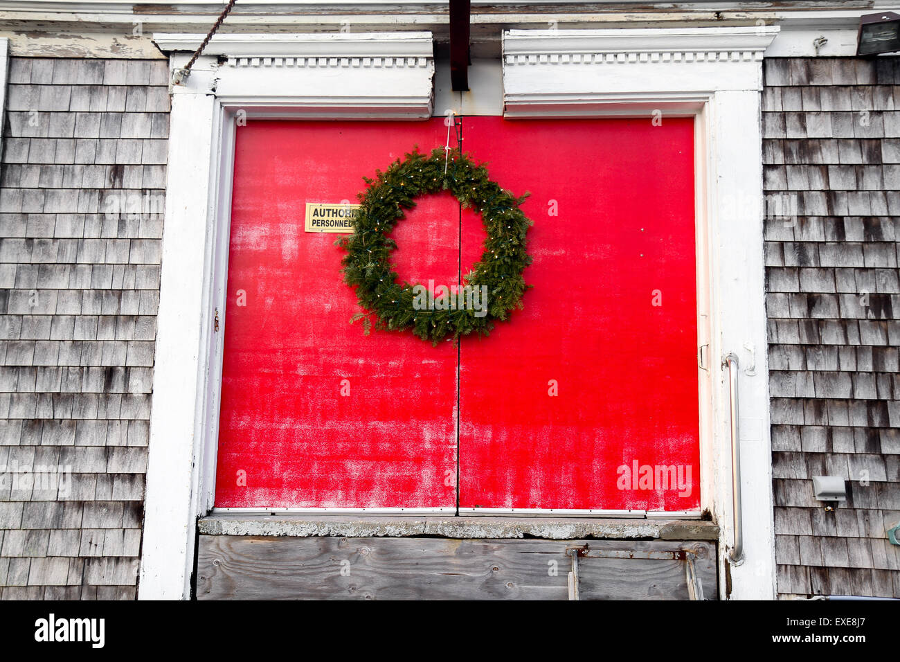 A holiday wreath on the red doors of a building at the Millway Marina, Barnstable Harbor, Barnstable, Cape Cod - Stock Image