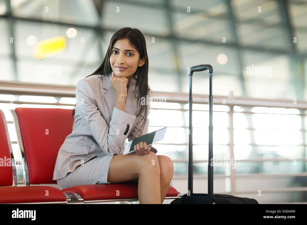 pretty Indian businesswoman waiting at airport for her flight - Stock Image