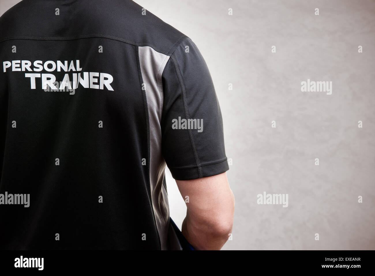 Personal Trainer, with his back facing the camera, in a grey background - Stock Image