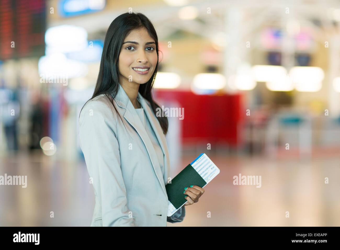 portrait of pretty Indian female business traveller at airport - Stock Image