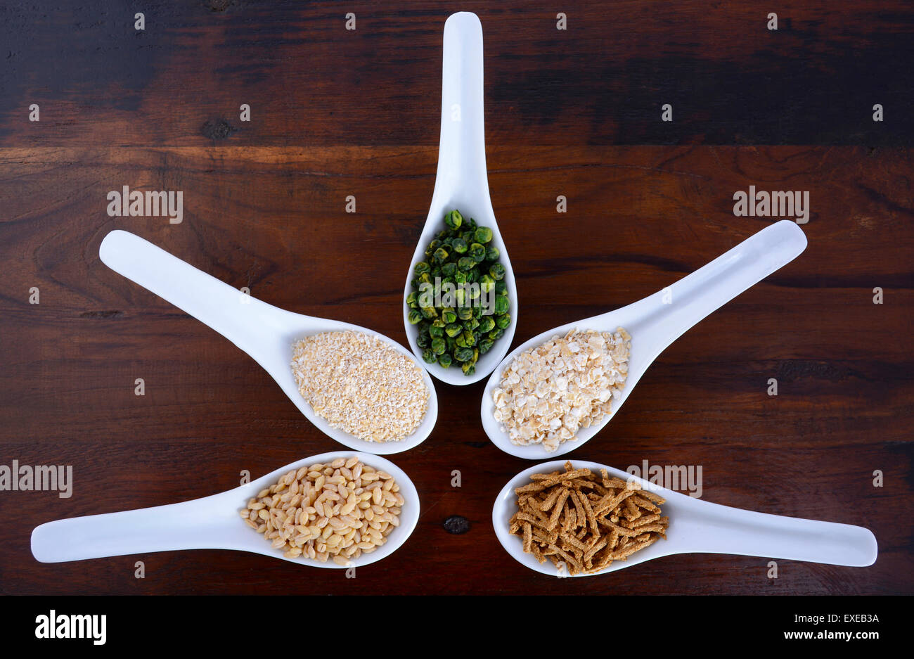 Healthy High Fiber Prebiotic Grains in serving spoons, including wheat bran cereal, oat flakes, dried legume peas, - Stock Image