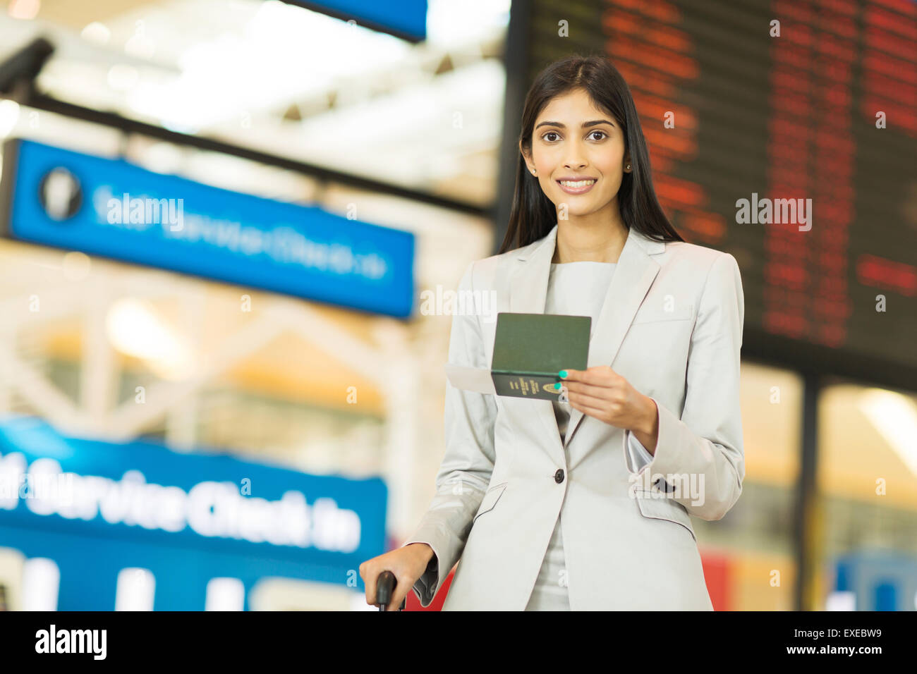 business traveller holding passport and boarding pass in front of flight information board at airport - Stock Image