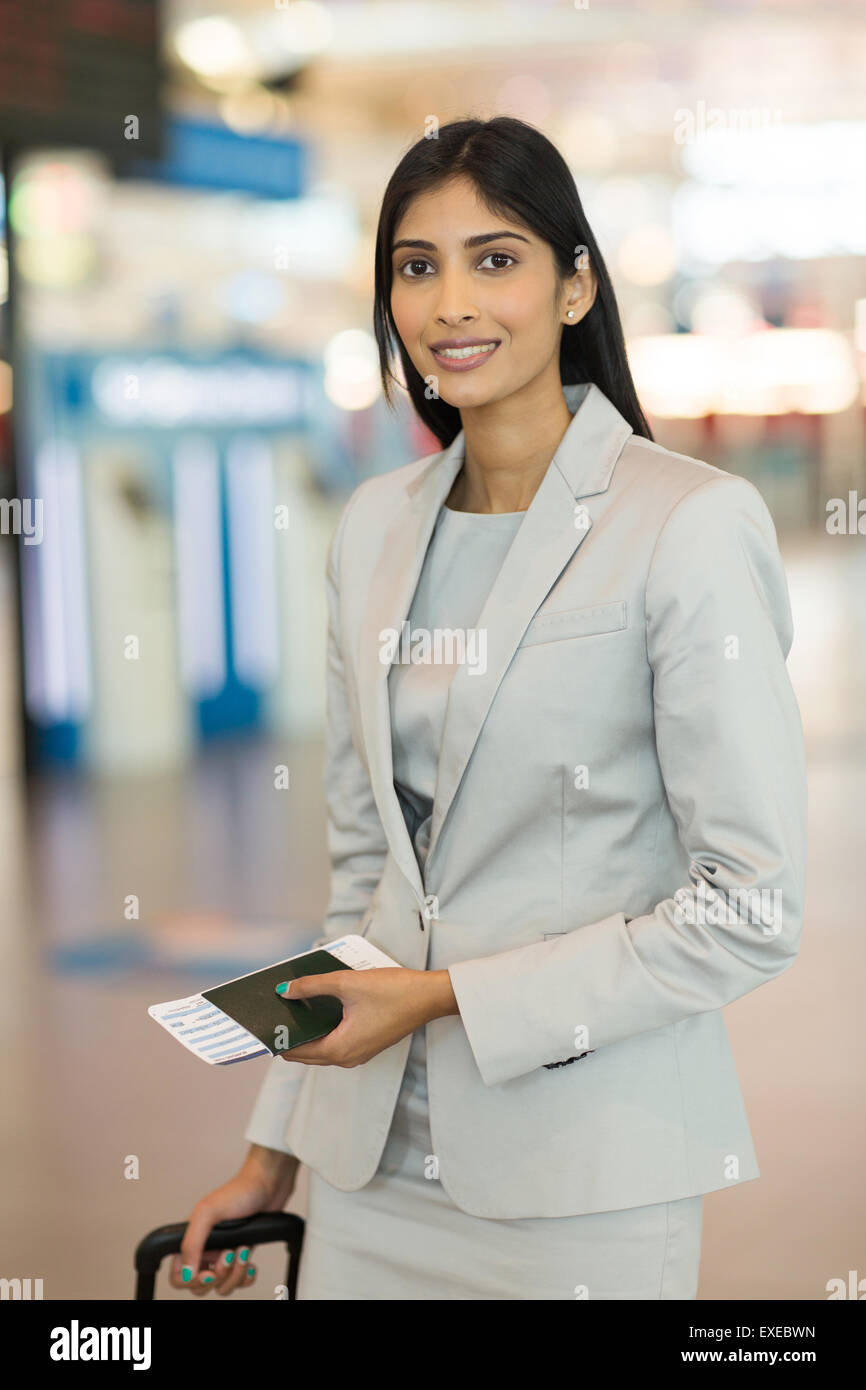 young business woman with passport and air ticket standing in airport - Stock Image