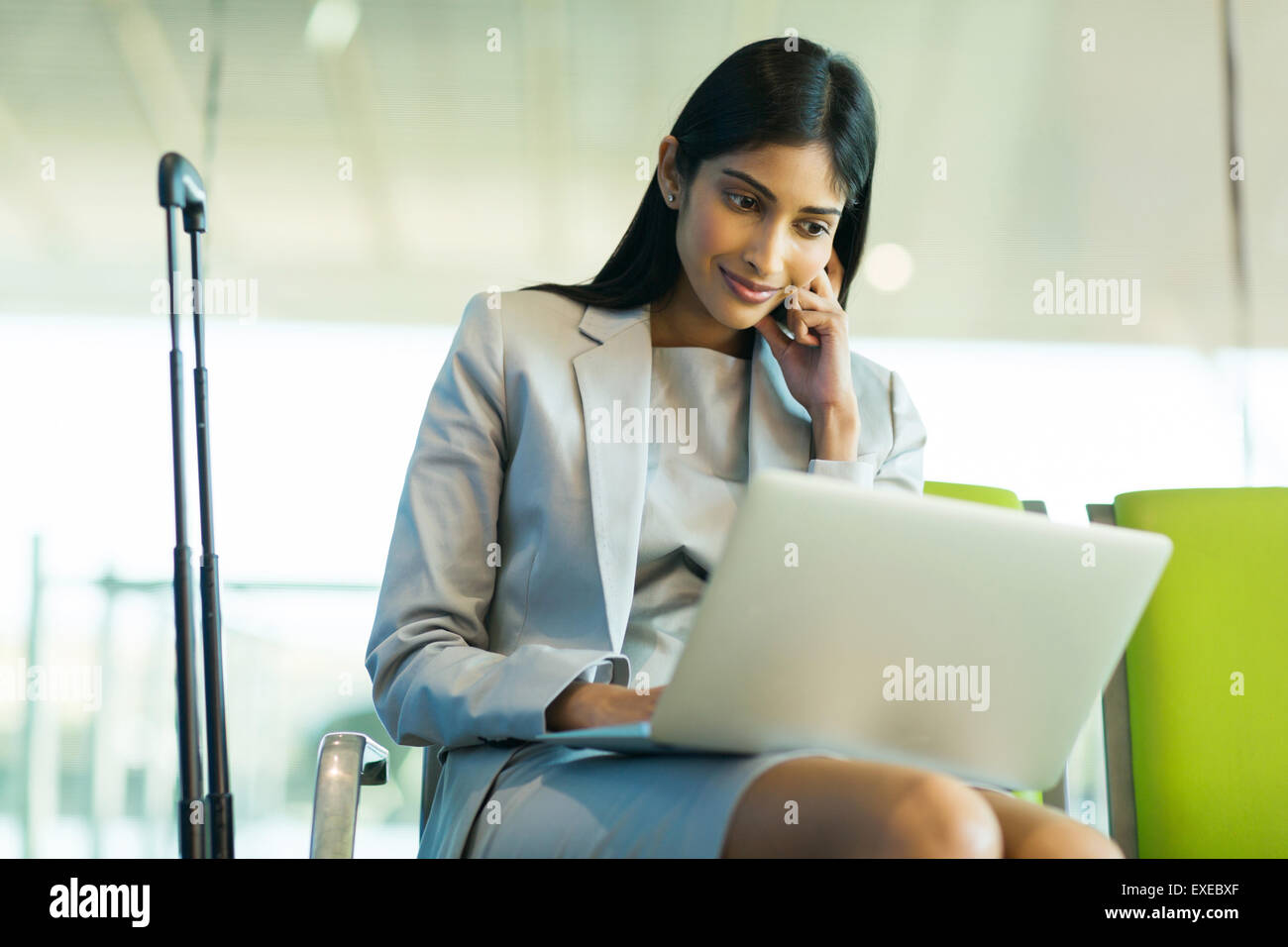 successful Indian businesswoman using laptop computer at airport - Stock Image