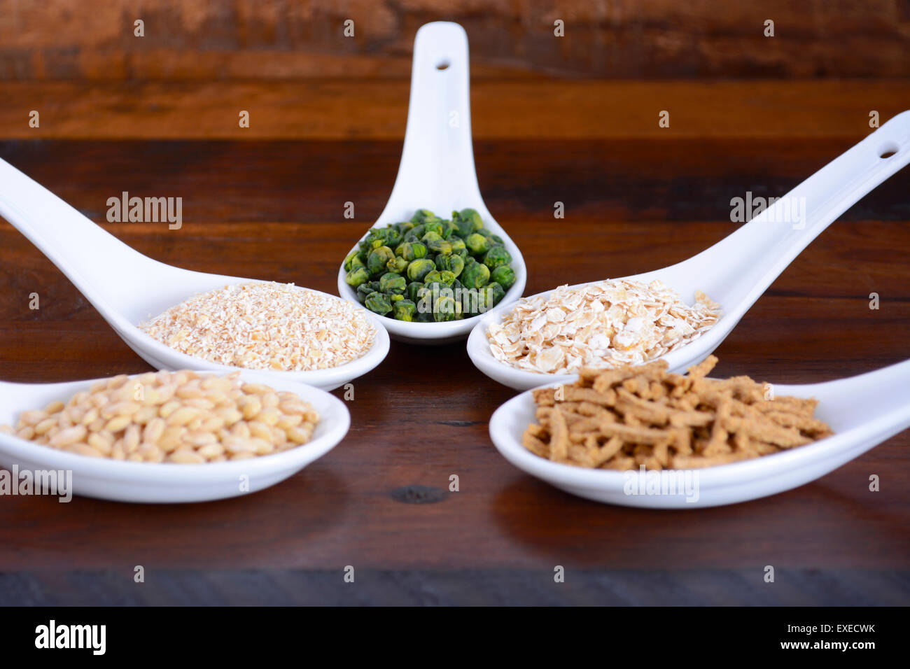 Healthy High Fiber Prebiotic Grains in serving spoons, including wheat bran cereal, oat flakes, dried legume peas, Stock Photo