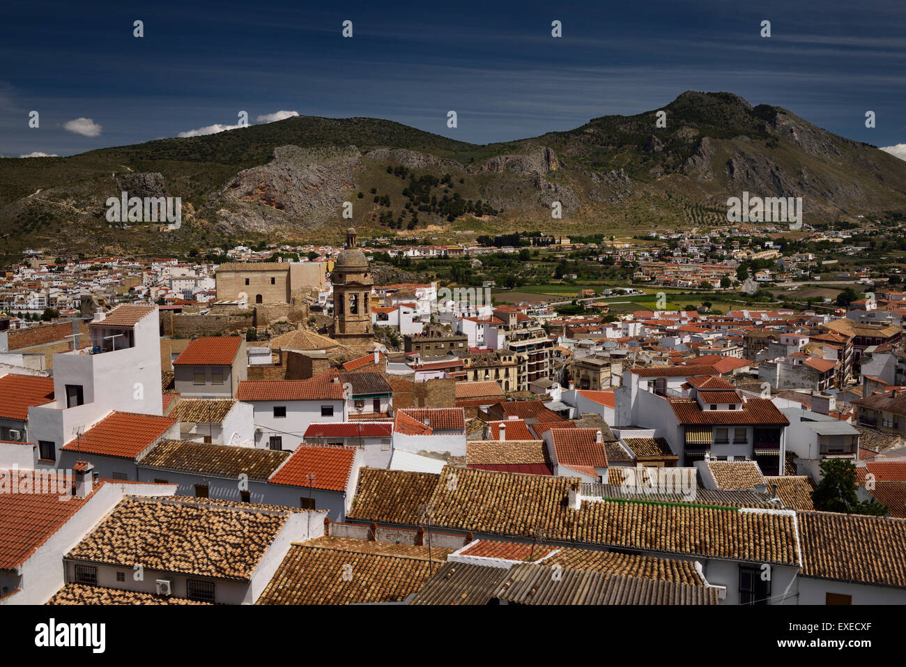 Overview of rooftop tiles with Church of the Incarnation and Gorda Peak at Loja Granada Spain - Stock Image