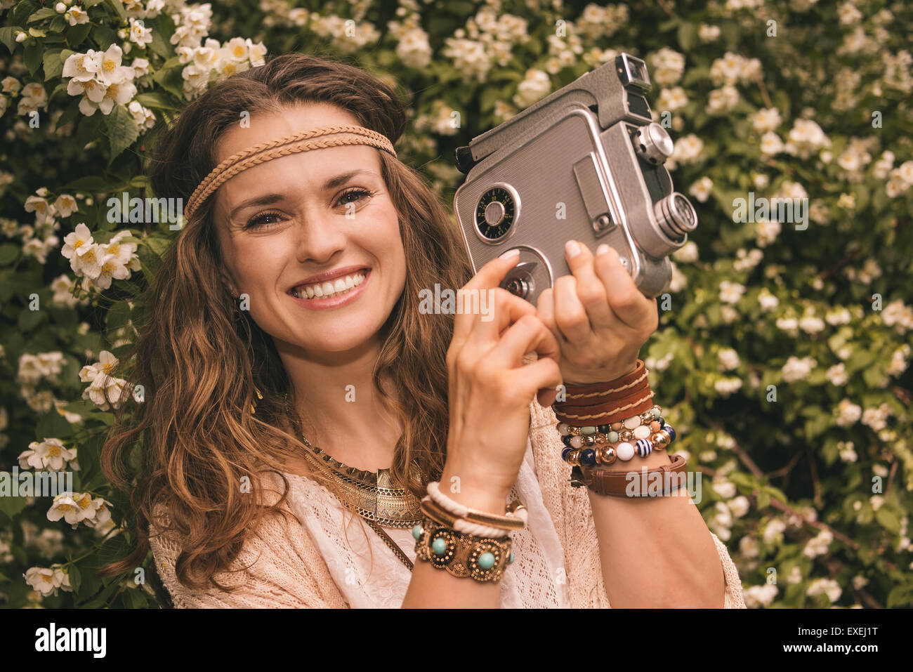 Longhaired hippy-looking young lady in knitted shawl and white blouse standing among flowers with retro camera Stock Photo