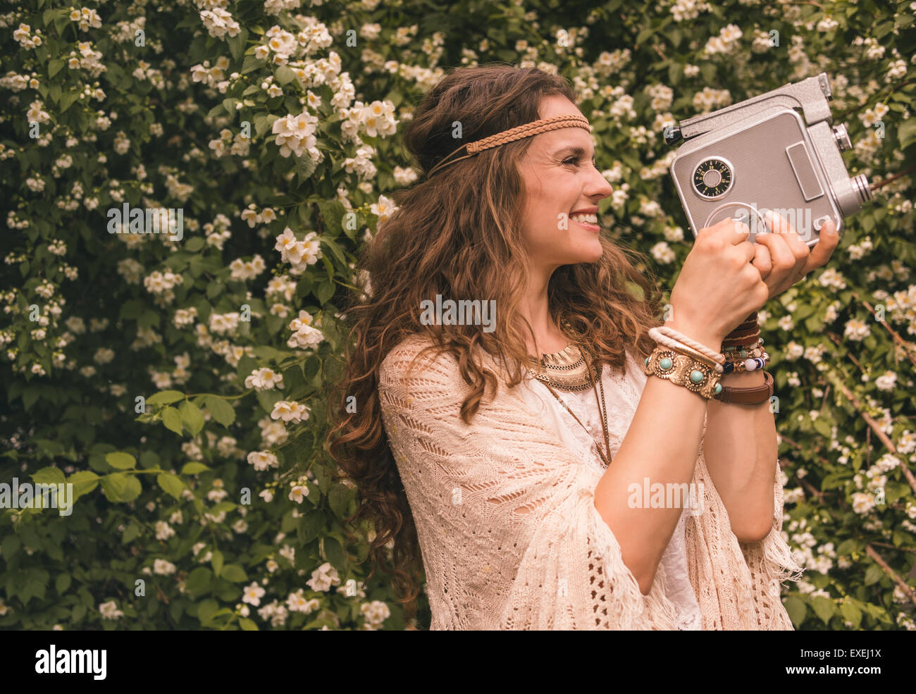 Longhaired hippy-looking young lady in knitted shawl and white blouse standing among flowers and using retro camera Stock Photo