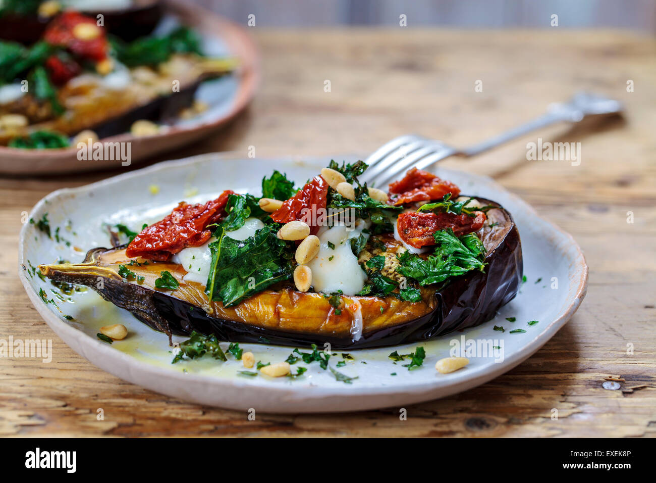 Roast aubergine with goat cheese, crispy kale, sun dried tomatoes and pine nuts - Stock Image