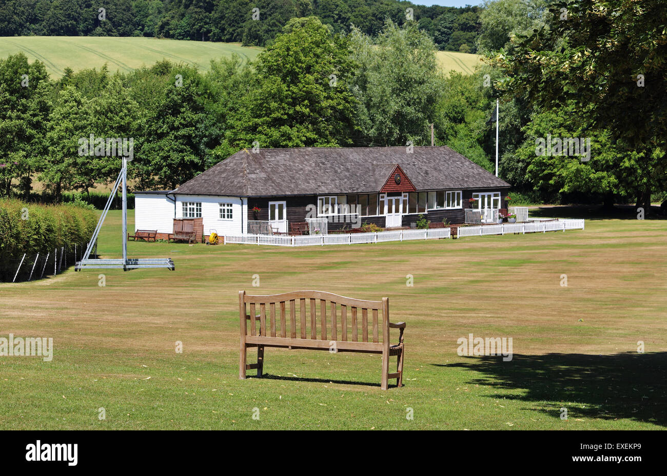 Traditional English Cricket field and Pavilion with bench seat in the foreground - Stock Image
