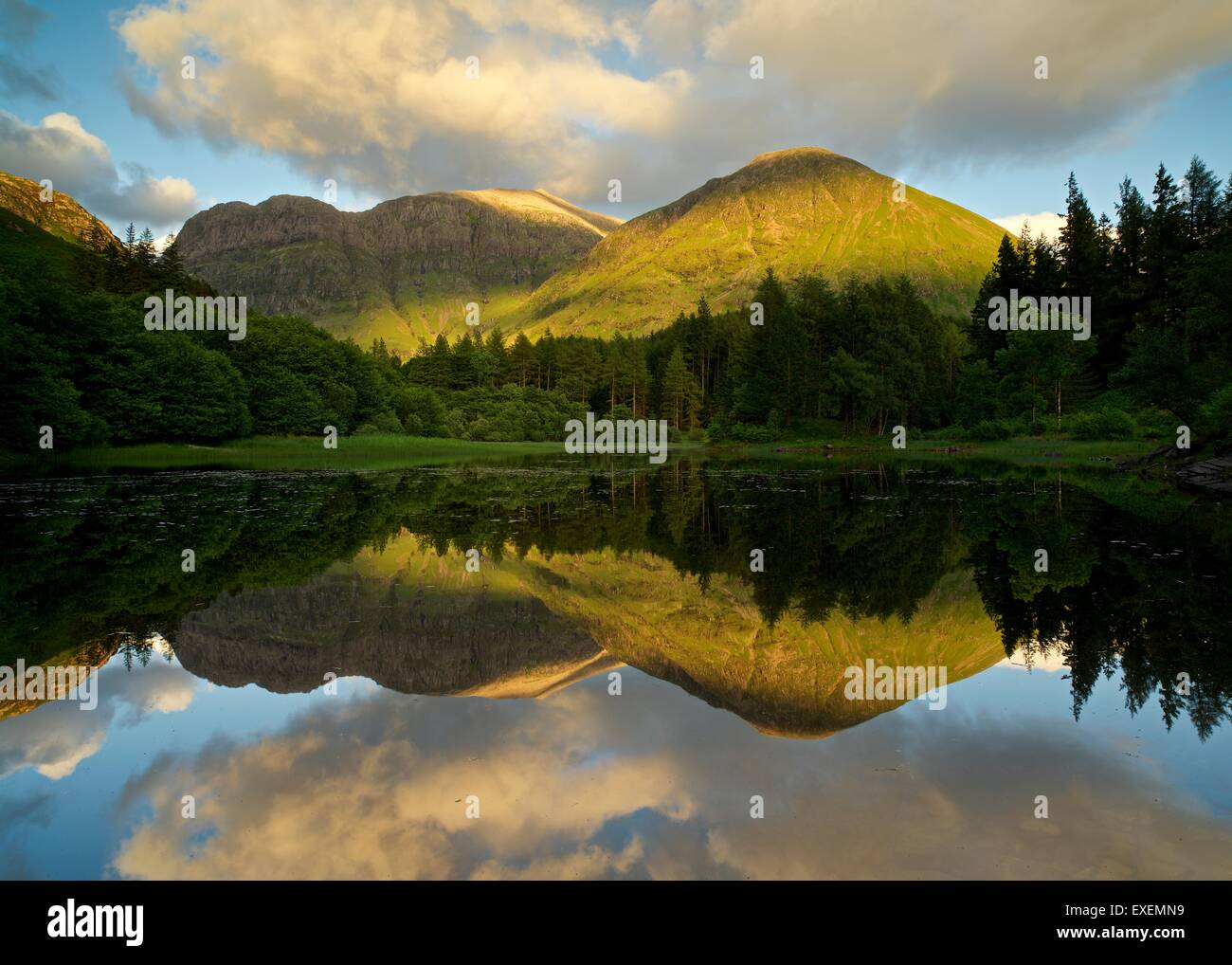 The low dipping sun casts a golden glow on the mountains of Glencoe whilst being reflected in the still Torren Loch - Stock Image