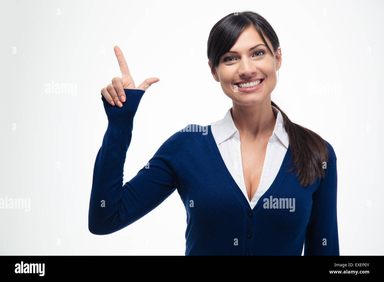 Smiling businesswoman pointing finger up isolated on a white background. Looking at camera - Stock Image
