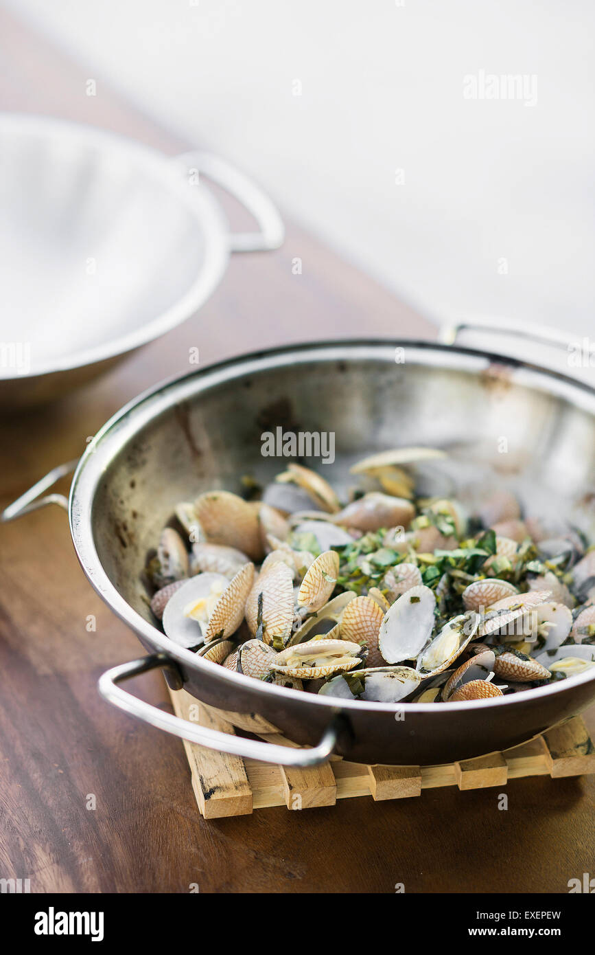 steamed mussels bulhao pato style with garlic and herb sauce in portuguese cataplana - Stock Image