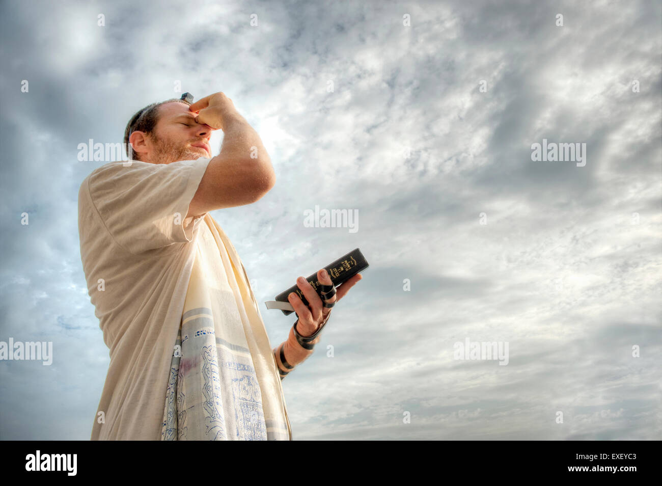 Jewish man engaged in morning prayers. - Stock Image