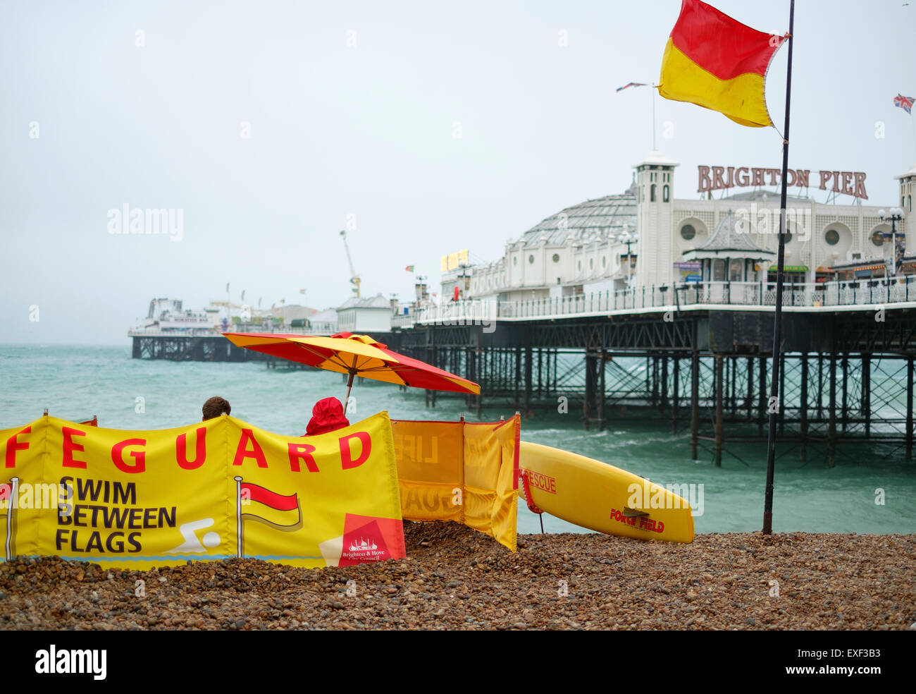 Brighton, UK. 13th July, 2015. UK Weather: An unseasonly wet, windy and cool day at the British seaside - lifeguards - Stock Image