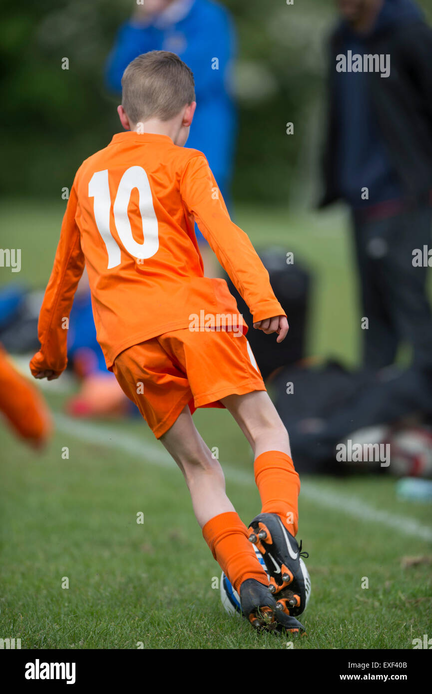 Young boy playing Sunday league football - Stock Image