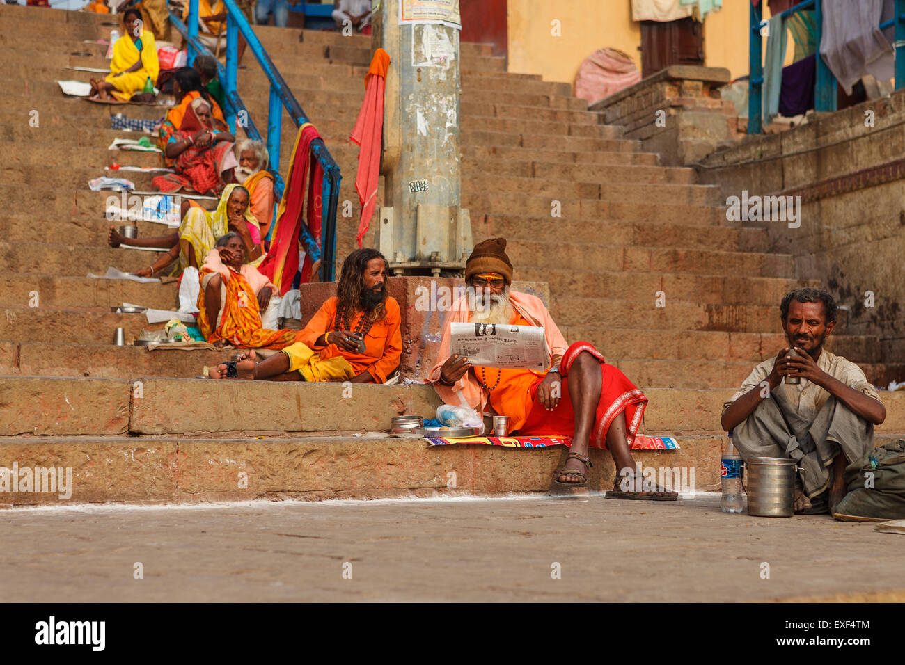 Sadhu ,whit-in his traditional dress, comfortably sits and reads Indian newspaper - Stock Image