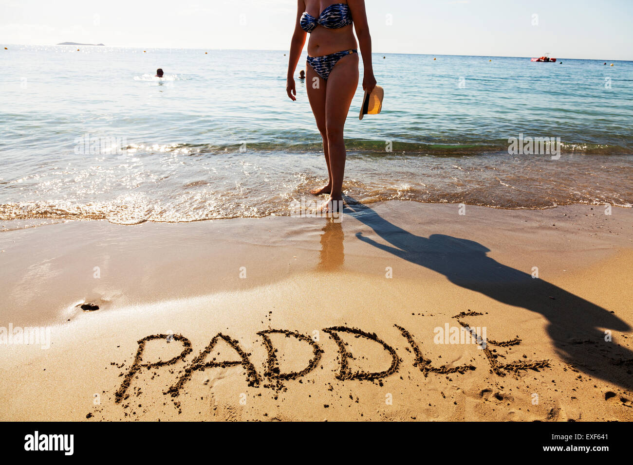 Paddle paddling feet in sea word written in sand on beach coast coastline Ibiza Spain Spanish Santa Eulalia Del - Stock Image