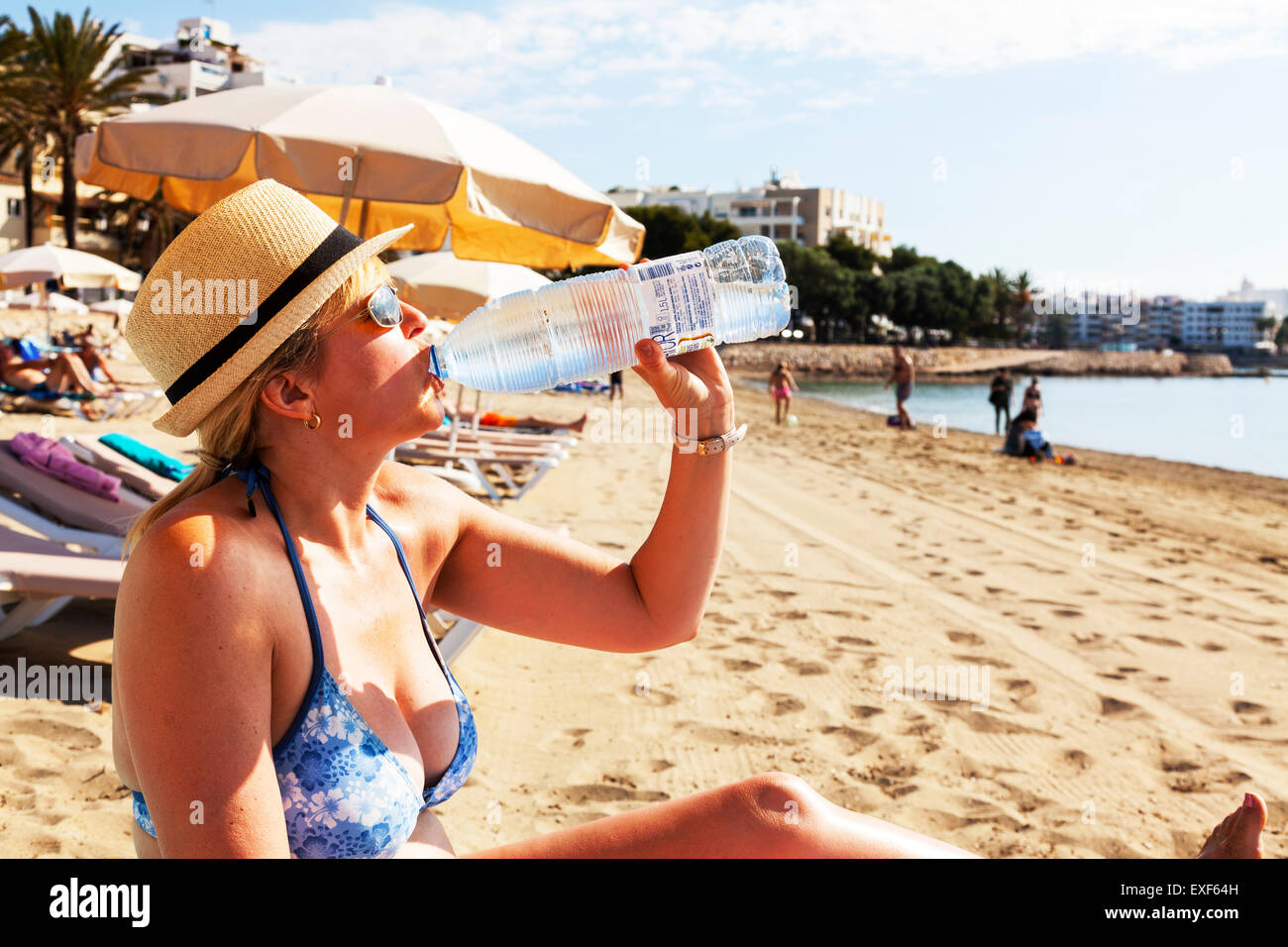 drinking drink water from bottle hydrating bottled rehydrate rehydrating sun sunny summer thirst thirsty Ibiza Spain - Stock Image