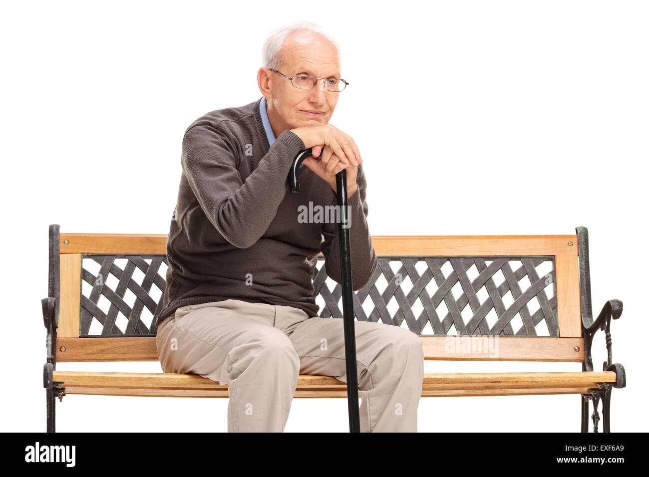 Studio shot of a pensive senior gentleman sitting on a bench and thinking isolated on white background - Stock Image