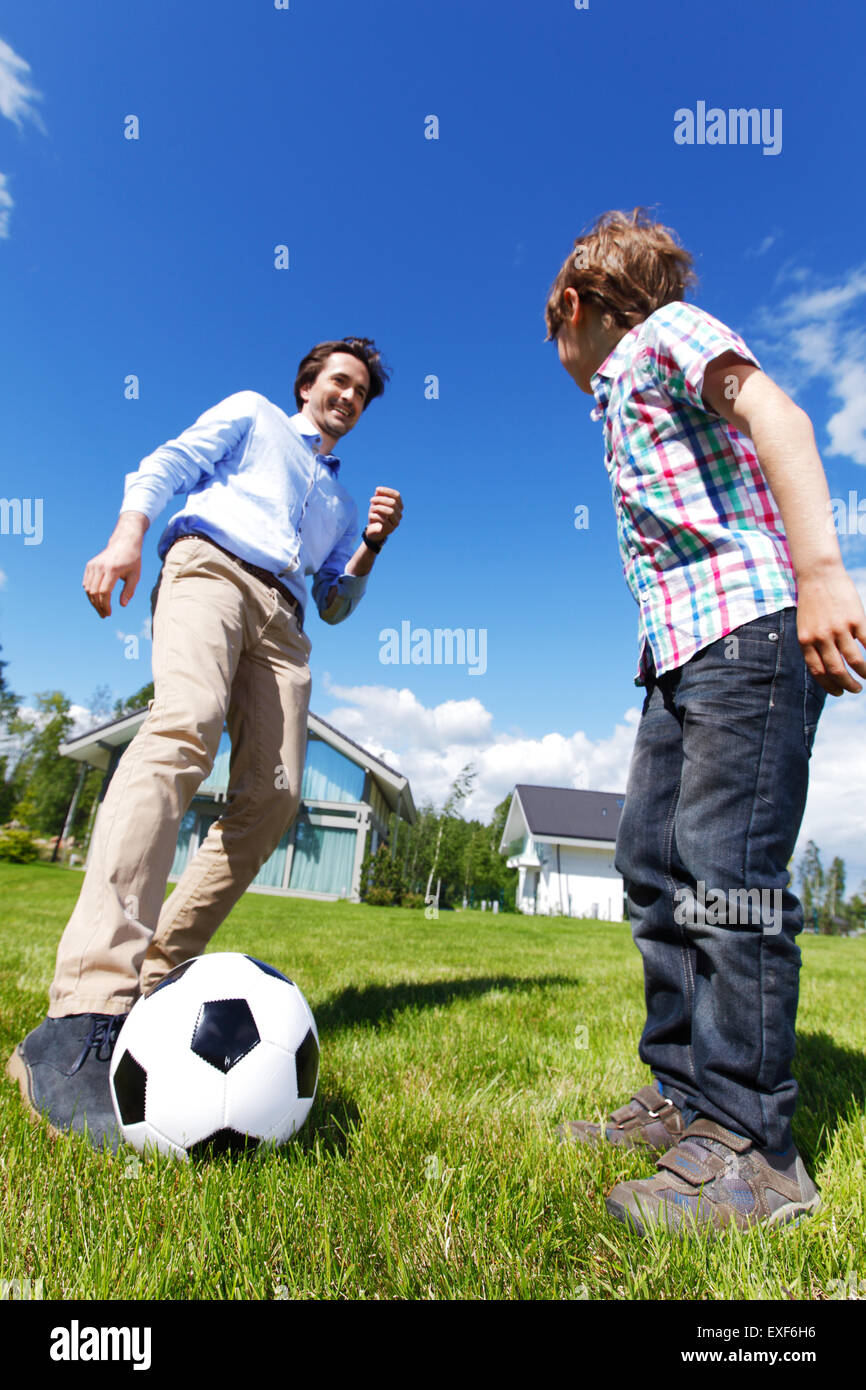 father and son playing football - Stock Image
