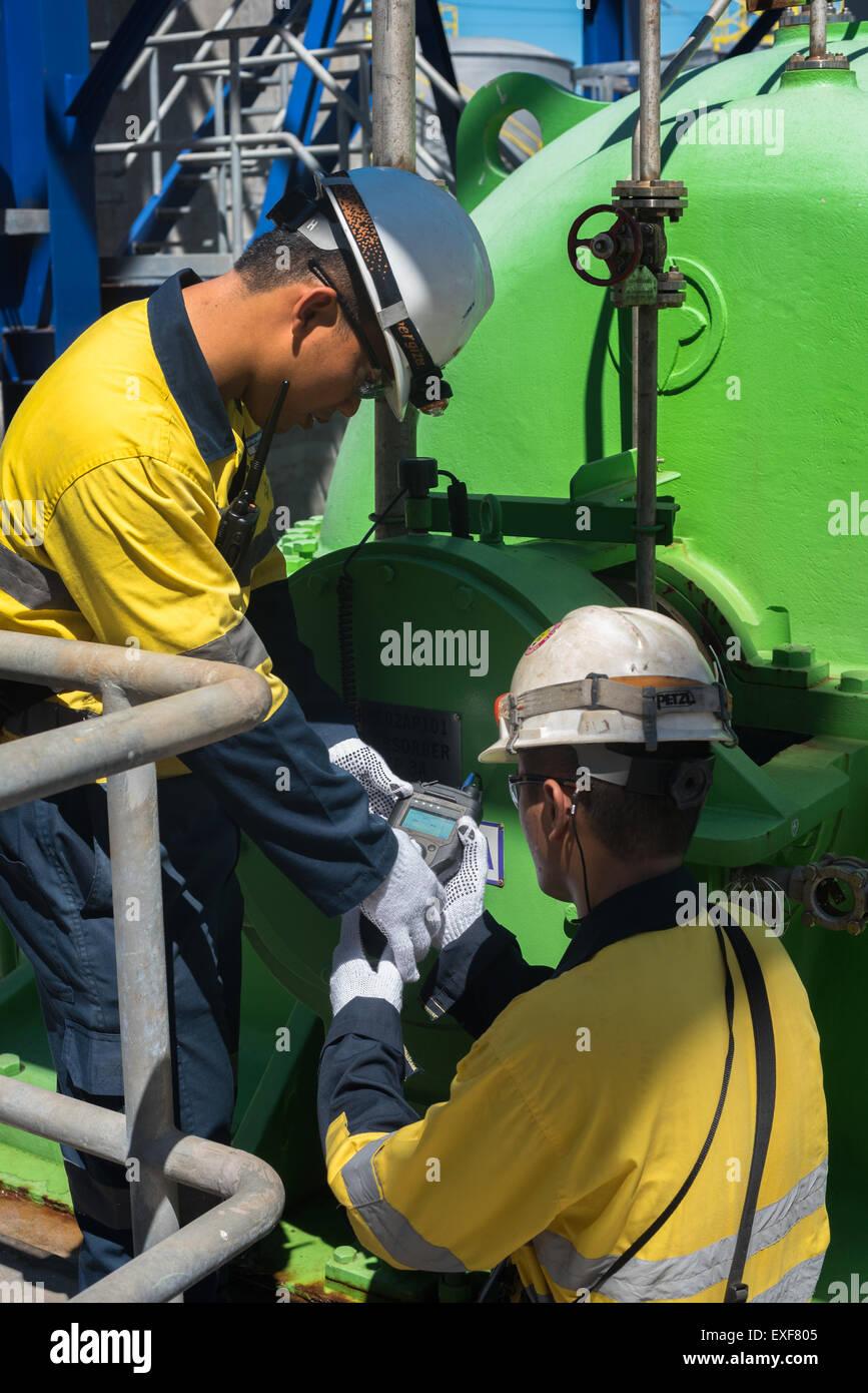 Men using digital gadget in power plant facility. - Stock Image