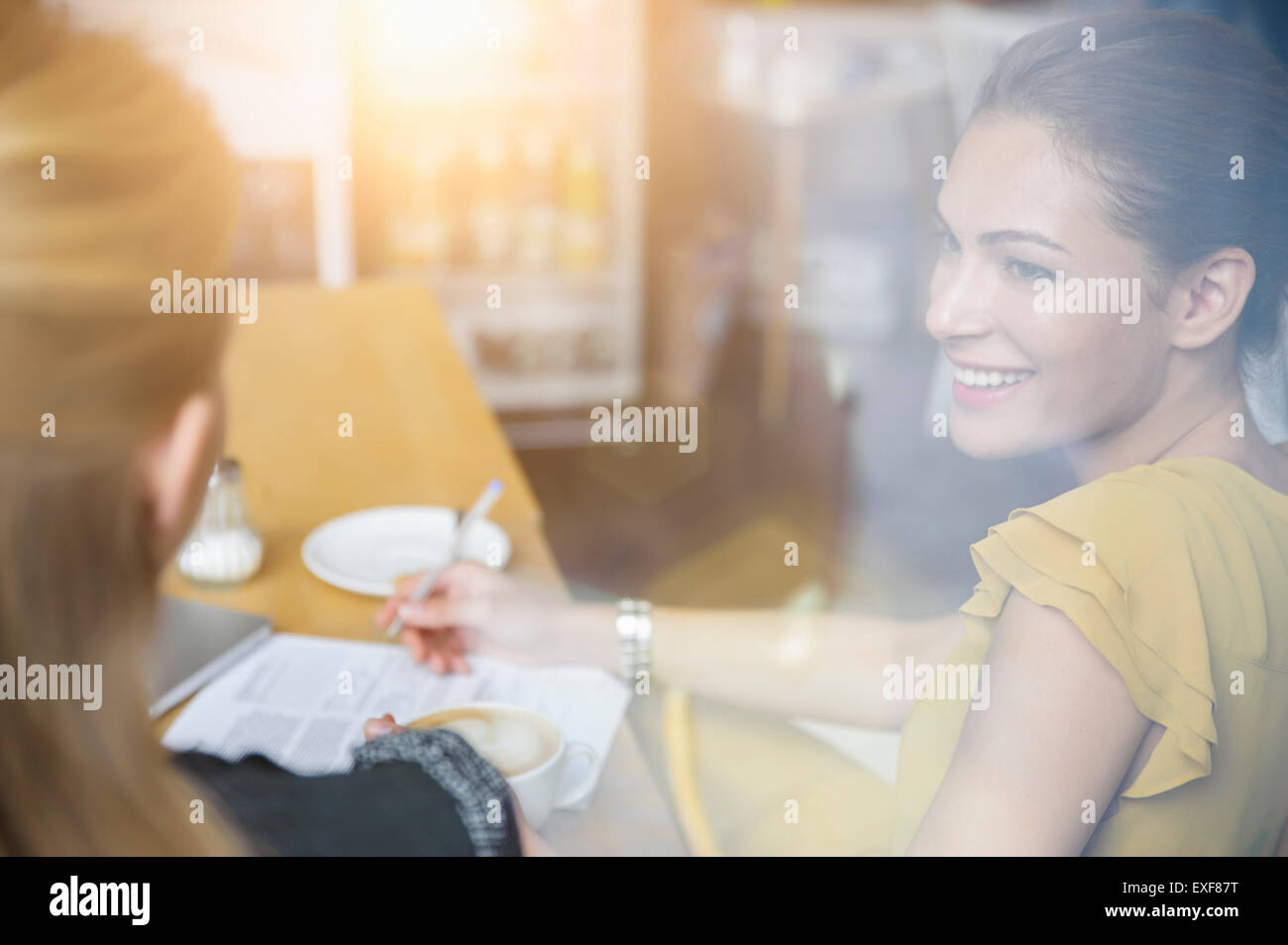Two female friends having coffee together in cafe - Stock Image
