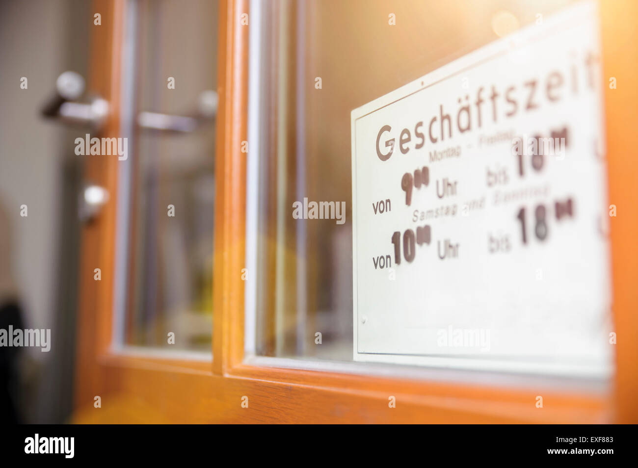 Opening hours sign on door of cafe - Stock Image