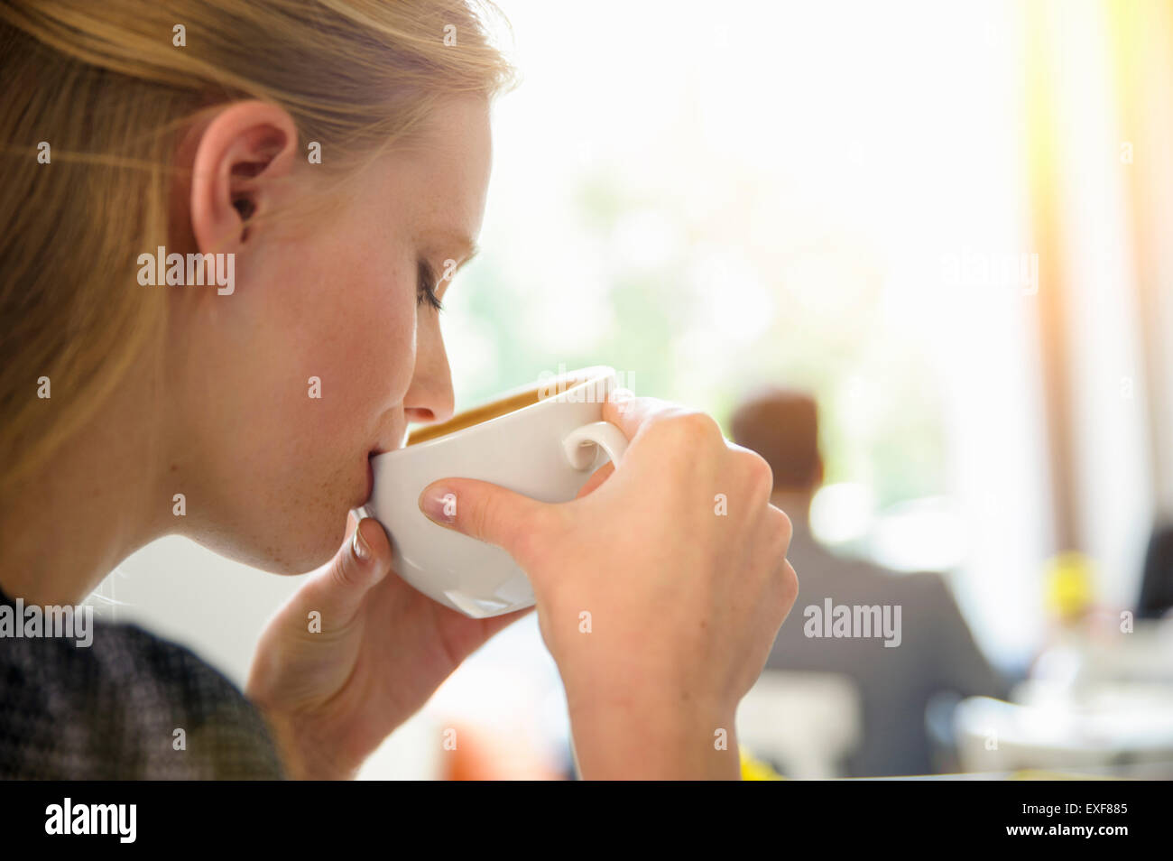 Young woman drinking coffee in cafe, close-up - Stock Image