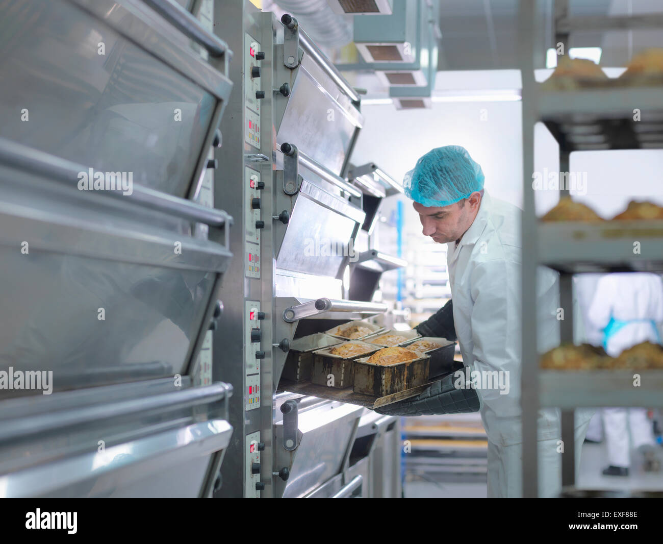 Baker taking cakes out of oven in cake factory - Stock Image